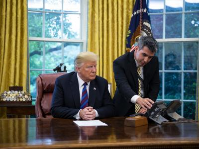 A White House aide assists Donald Trump connect a phone call with Enrique Pena Nieto on Aug. 27. Photographer: Al Drago/Bloomberg